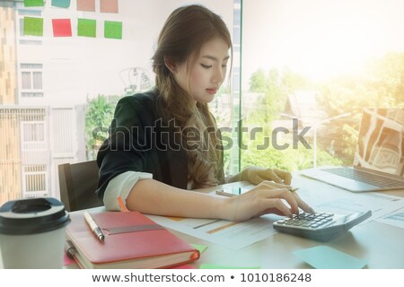 businesswoman using laptop and calculator at office desk and man stock photo © Freedomz