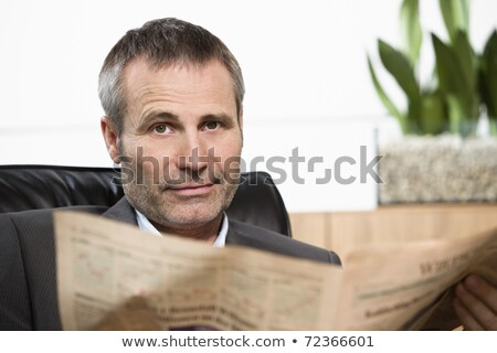 Smiling businessman reading newspaper looking straight. Stock photo © lichtmeister