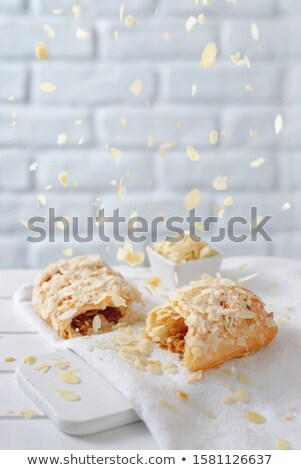 Almond flakes falling from above over caramel strudel Stock photo © georgemuresan