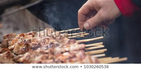 Man cooking marinated shashlik, lamb meat grilling on metal skew Stock photo © dashapetrenko