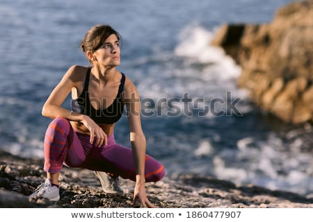 A woman performs warm-up and sports exercises on the beach in the active recreation area Stock photo © ElenaBatkova