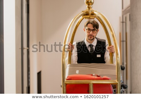 Young elegant porter in eyeglasses pushing cart with luggage of hotel guests Stock photo © pressmaster