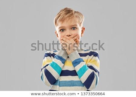 shocked boy closing mouth by hands Stock photo © dolgachov