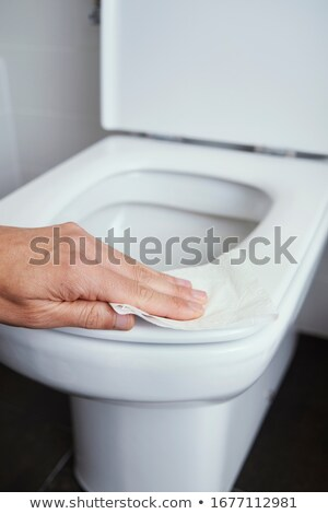 man cleaning the toilet seat with a piece of paper Stock photo © nito