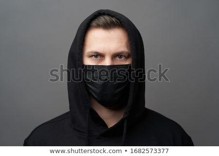 Portrait of man wearing black mask at grey background. Stock photo © Illia