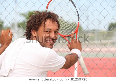Male tennis player leaning on the fence of a municipal hard court Stock photo © photography33