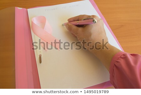 Woman hand with  red folder laying on it stock photo © Olesha
