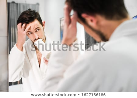 the young handsome drying his hair isolated on white stock photo © elnur
