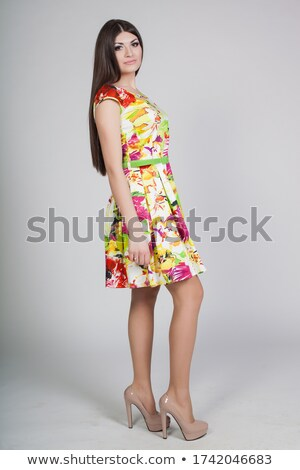 serious woman posing in red dress with hands on hips stock photo © deandrobot