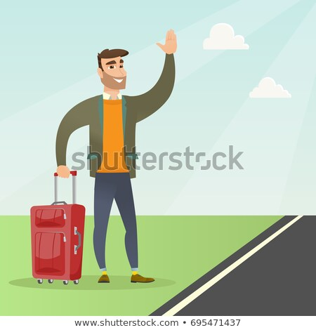Young caucasian man with a suitcase hitchhiking. Stock photo © RAStudio