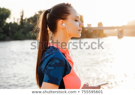 Woman listening to music by river Stock photo © IS2