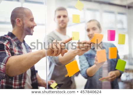 businesswoman sticking notes on window stock photo © is2