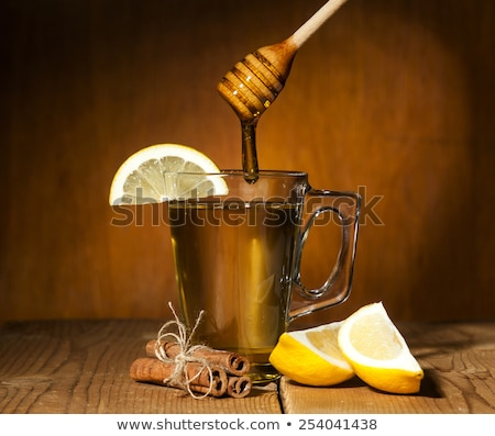 Stock photo: honey drops from a honey dipper in glass cup with green tea