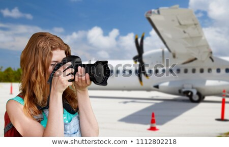 tourist woman photographing by camera over plane Stock photo © dolgachov