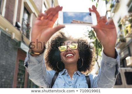 молодые · черную · женщину · Постоянный · улыбаясь · городской · улице · здании - Сток-фото © Stasia04