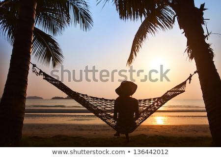 ストックフォト: 女性 · 帽子 · 座って · ビーチ · 日没 · 時間