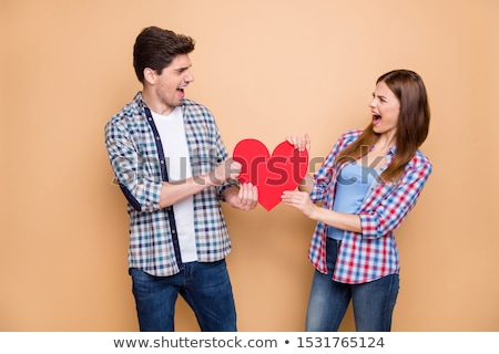 angry casual woman pulling by a big red heart  Stock photo © feedough