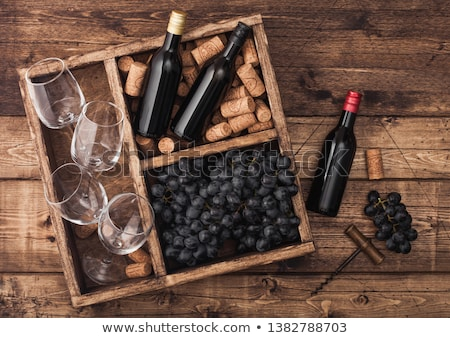 Foto d'archivio: Mini Bottles Of Red Wine And Empty Glasses With Dark Grapes With Corks And Opener Inside Vintage Woo