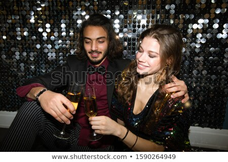 Young affectionate couple clinking with champagne at party in night club Stock photo © pressmaster
