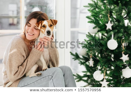 Horizontal shot of caring smiling woman hugs puppy with love, enjoys cozy atmopshere and lovely mome Stock photo © vkstudio