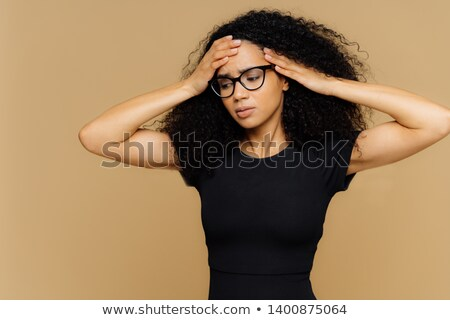 Half length shot of stressful woman with Afro hairstyle, focused down, touches head, suffers from mi Stock photo © vkstudio