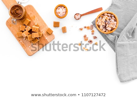 Glass bowl of natural brown caramelized sugar cubes on white background. Stock photo © DenisMArt