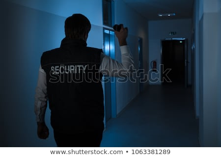 Security Guard With Flashlight In Building Corridor Stock photo © AndreyPopov
