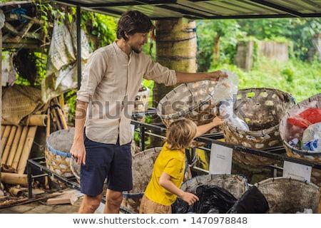 Dad and son, separate garbage collection. Teaching children to separate garbage collection Stock photo © galitskaya