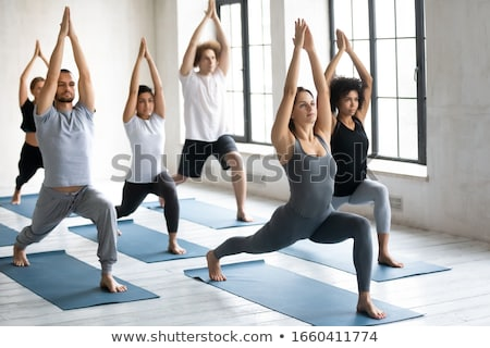 Young woman performing stretching exercise on yoga mat stock photo © wavebreak_media