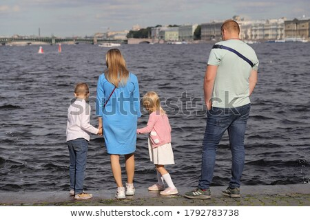 Stock photo: Happy family with little girl splashes water hands standing on b