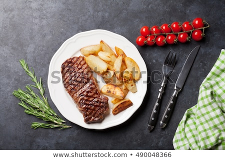 Cut sirloin beef on a plate with fork and knife Stock photo © shutswis