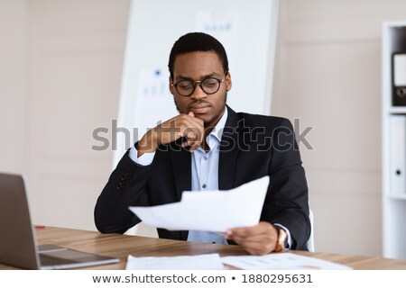 Stock photo: Young troubled businessman in front of his laptop