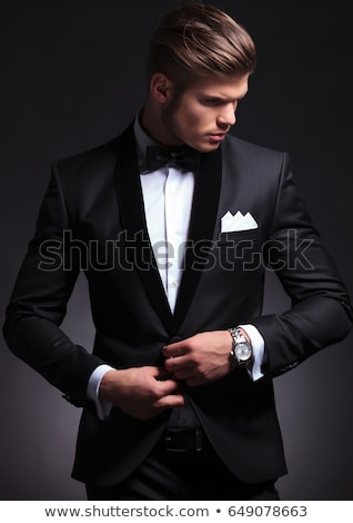 elegant man unbuttoning his suit and looks to side  Stock photo © feedough