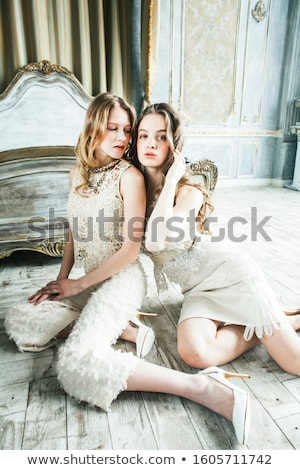 Stock photo: two pretty twin sister blond curly hairstyle girl in luxury house interior together, rich young peop