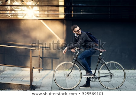 man with bicycle and headphones on city street Stock photo © dolgachov