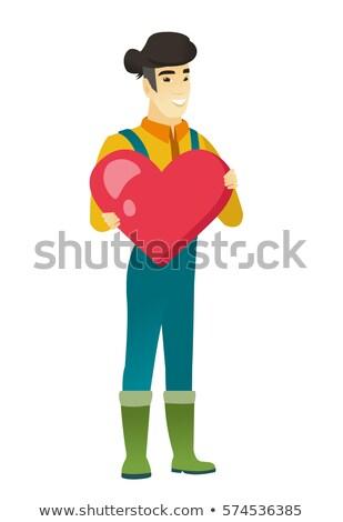 Asian farmer holding a big red heart. Stock photo © RAStudio