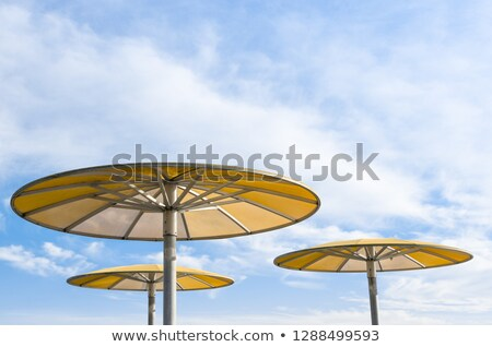 Foto stock: Three Yellow Parasols Against Blue Sky