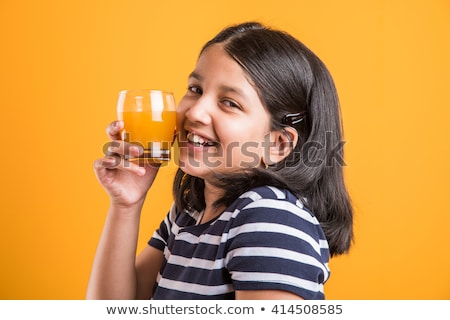 Cute cheveux noirs petite fille potable jus d'orange manger Photo stock © boggy