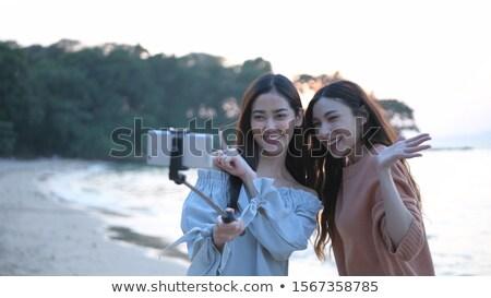 Jovem Ásia mulher telefone móvel praia pôr do sol Foto stock © galitskaya