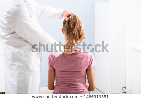 physician giving neck massage to his patient stock photo © andreypopov