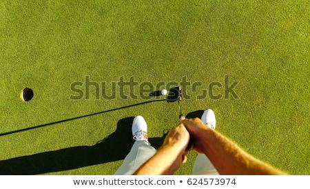 Male golfer putting golf ball on the green golf Stock photo © Kzenon