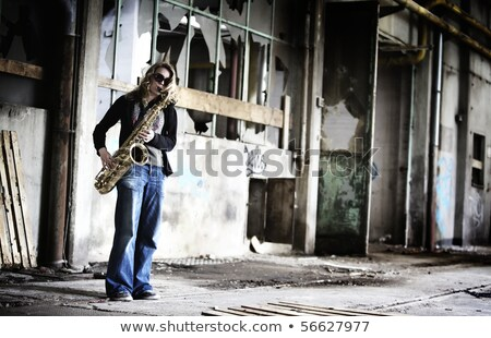 Girl playing saxophone in old factory hall. Stock photo © lichtmeister