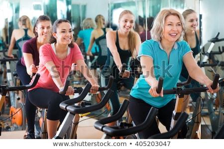 senior woman on an exercise bike in the gym stock photo © kzenon