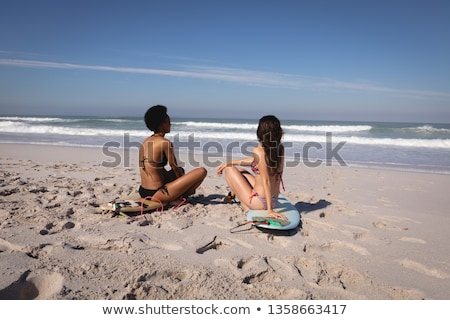 Rear view of young multi ethnic women sitting on surfboard in front of the sea at beach in the sunsh Stock photo © wavebreak_media