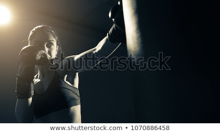 Image of focused woman wearing sportswear training in boxing hand wraps Stock photo © deandrobot
