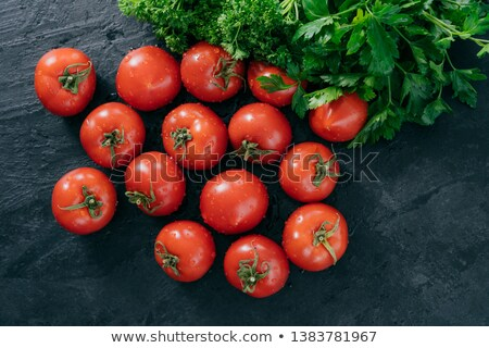 Spring vitamins concept. Harvested red heirloom tomatoes and green parsley isolated over dark backgr Stock photo © vkstudio