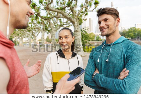 Photo of athletic smiling sportsman talking cellphone while working out Stock photo © deandrobot