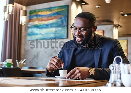 portrait of a young man drinking coffee and looking at camera s stock photo © hasloo