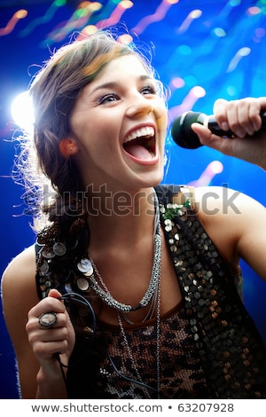 Portrait of a glamorous girl holding a mike and singing Stock photo © HASLOO
