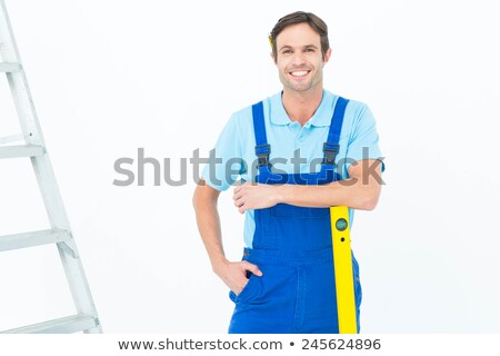 Confident handyman leaning on a ladder stock photo © lightkeeper